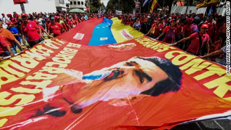 Supporters of Venezuelan President Nicolas Maduro hold a giant flag during a demonstration in Caracas on October 18, 2016. Venezuela's Supreme Court has raised another obstacle to an opposition drive for a referendum on recalling leftist President Nicolas Maduro, who is blamed for a deepening economic and political crisis. / AFP / JUAN BARRETO        (Photo credit should read JUAN BARRETO/AFP/Getty Images)