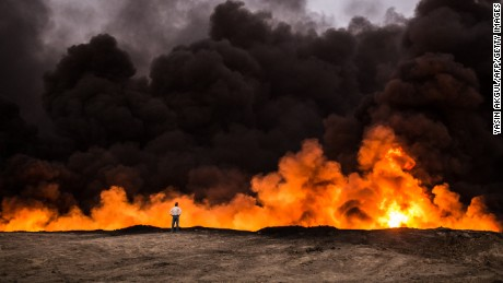 A man stands in front of a fire from oil that has been set ablaze in the Qayyarah area by ISIS, on October 19.