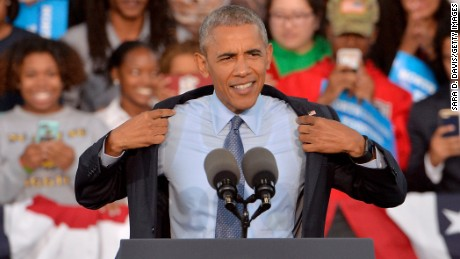 President Barack Obama takes off his suit coat after seeing the large crowd during a campaign event for Democratic presidential nominee Hillary Clinton on October 11, 2016 in Greensboro, North Carolina.