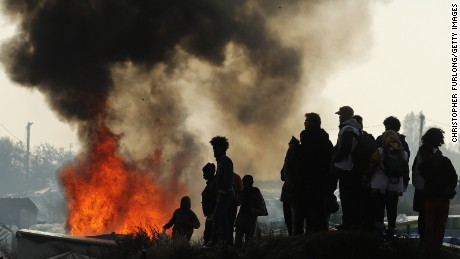 Fire takes hold in the notorious Jungle camp as migrants leave and the authorities demolish the site on October 26, 2016 in Calais, France.