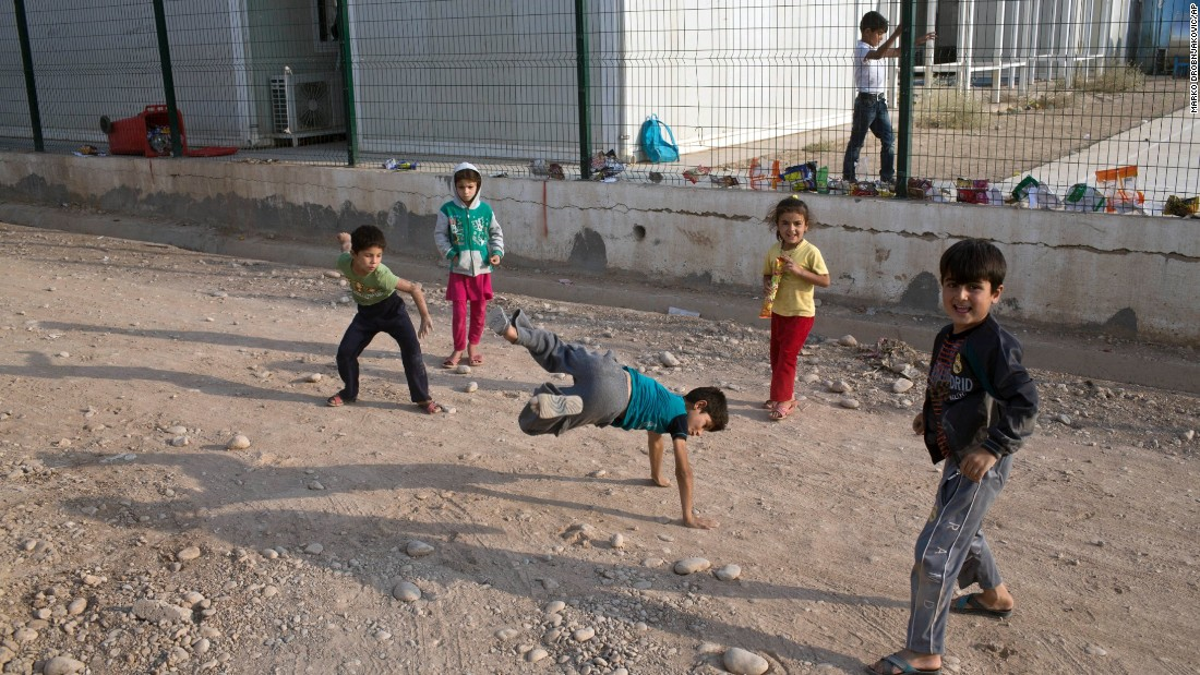Children dance and play inside the Baharka camp outside Irbil on October 25. The camp is for those displaced by the fighting.