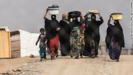 Iraqi families, who were displaced by the ongoing operation by Iraqi forces against jihadistds of the Islamic State group to retake the city of Mosul, walk at a camp for displaced people near Qayyarah on October 24, 2016.