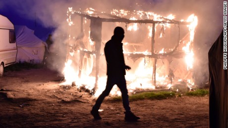 "TOPSHOT - A migrant walks past a shack set on fire during the demolition of the Calais ""Jungle"" camp, in Calais, northern France, on October 25, 2016 as hundreds of migrants boarded buses on the second day of a massive operation to clear the squalid settlement. More than 1,900 left the slum on October 24, ahead of work to tear down the makeshift shelters and eateries in the camp that has become a symbol of Europe's refugee crisis. / AFP / PHILIPPE HUGUEN        (Photo credit should read PHILIPPE HUGUEN/AFP/Getty Images)"
