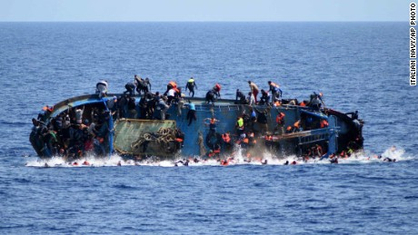 FILE - In this May 25, 2016 file photo made available by the Italian Navy, people try to jump in the water right before their boat overturns off the Libyan coast. Over 700 migrants are feared dead in three Mediterranean Sea shipwrecks south of Italy in the last few days as they tried desperately to reach Europe in unseaworthy smuggling boats, the U.N. refugee agency said Sunday, May 29, 2016. (Italian navy via AP Photo, file)