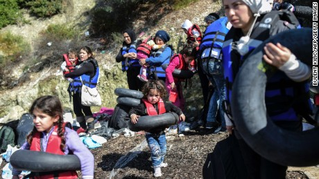 """Syrian migrants wear life-jackets and  life-belts before boarding a dinghy to cross the Aegean Sea to the Greek island of Lesbos from the Ayvacik coast in Canakkale on February 28, 2016. The number of asylum-seekers entering Greece from Turkey continues unabated and the border closures along the Balkan route """"are creating a difficult situation in Greece,"""" UN Secretary-General Ban Ki-moon saif on February 26, 2016. Close to 120,000 migrants have already arrived in Europe so far this year, according to the UN refugee agency. / AFP / BULENT KILIC        (Photo credit should read BULENT KILIC/AFP/Getty Images)"""