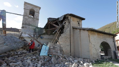 A photographer walks among debris from the Church of St. Antony, dating back to the XIV century, in the small town of Visso in central Italy, Thursday, Oct 27, 2016, after a 5.9 earthquake destroyed part of the town. A pair of strong aftershocks shook central Italy late Wednesday, crumbling churches and buildings, knocking out power and sending panicked residents into the rain-drenched streets just two months after a powerful earthquake killed nearly 300 people. (AP Photo/Alessandra Tarantino)