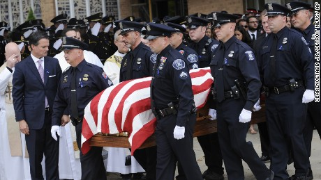 Pallbearers carry the casket of Sgt. Ken Steil at the end of his funeral service in St. Clair Shores, Mich., Friday, Sept. 23, 2016. Detroit's police chief on Friday posthumously promoted Steil, a 20-year veteran officer, who died five days after being shot while chasing a suspect.