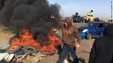 Demonstrators stand next to burning tires as armed soldiers and law enforcement officers assemble on Thursday, Oct. 27, 2016, to force Dakota Access pipeline protesters off private land where they had camped to block construction. The pipeline is to carry oil from western North Dakota through South Dakota and Iowa to an existing pipeline in Patoka, Ill.
