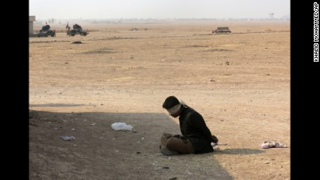 """A handcuffed suspected Islamic State militant sits outside his house as Iraq's elite counterterrorism forces fight against Islamic State militants, in the village of Tob Zawa, about 9 kilometers (5½ miles) from Mosul, Iraq, Tuesday, Oct. 25, 2016. Iraqi forces battled Islamic State fighters for a third day in a remote western town far from Mosul on Tuesday, but the U.S.-led coalition insisted the latest in a series of """"spoiler attacks"""" had not forced it to divert resources from the fight to retake Iraq's second-largest city. (AP Photo/Khalid Mohammed)"""