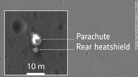 The zoomed insets provide close-up views of what are thought to be several different hardware components associated with the module's descent to the martian surface. These are interpreted as the front heatshield, the parachute and the rear heatshield to which the parachute is still attached, and the impact site of the module itself.