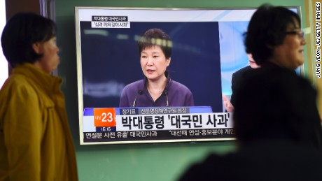 People walk past a television screen showing South Korean President Park Geun-Hye making a public apology, at a railway station in Seoul on October 25, 2016. South Korean President Park Geun-Hye was forced into a public apology on October 25 for the leak of official documents to a family associate involved in a growing corruption scandal. / AFP / JUNG YEON-JE        (Photo credit should read JUNG YEON-JE/AFP/Getty Images)