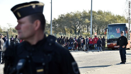 "French Gendarmes stand guard by migrants minors as they queue to enter a bus to be relocated in a reception and orientation centre (CAO), in Calais, on October 28, 2016 following a massive operation to clear the settlement of the ""Jungle"" Calais migrant camp where 6,000-8,000 people have been living. Dozens of migrant youths stranded for two days in the Calais ""Jungle"" as it was being demolished were offered transfers out of the camp on October 28, 2016 as France and Britain battled over who was to blame for their plight. The migrants, many of them minors, slept in some of the shelters left standing in a part of the slum that was razed in March, a prelude to this week's massive clearance of the camp.  / AFP / PHILIPPE HUGUEN        (Photo credit should read PHILIPPE HUGUEN/AFP/Getty Images)"