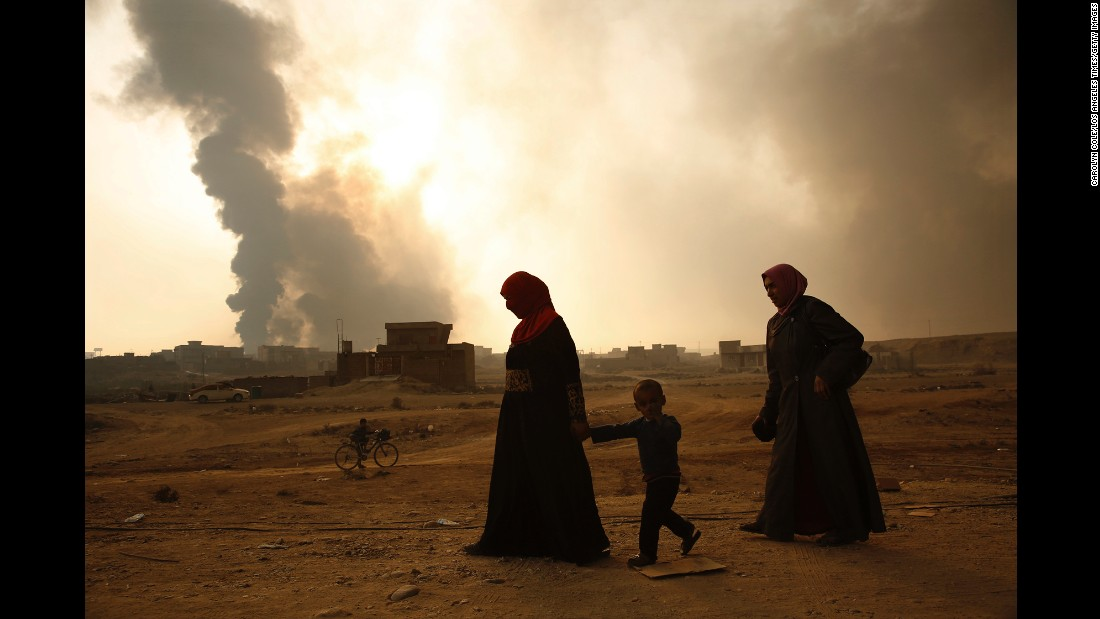 A family walks near billowing smoke from burning oil wells and sulfur fires that were set by ISIS fighters on October 26.