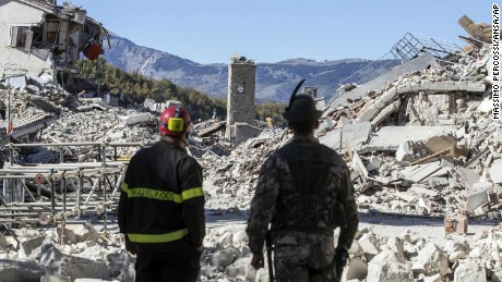 A firefighter, left, and an alpine soldier look at rubble in the hilltop town of Amatrice as an earthquake with a preliminary magnitude of 6.6 struck central Italy, Sunday, Oct. 30, 2016. A powerful earthquake rocked the same area of central and southern Italy hit by quake in August and a pair of aftershocks last week, sending already quake-damaged buildings crumbling after a week of temblors that have left thousands homeless. (Massimo Percossi/ANSA via AP)