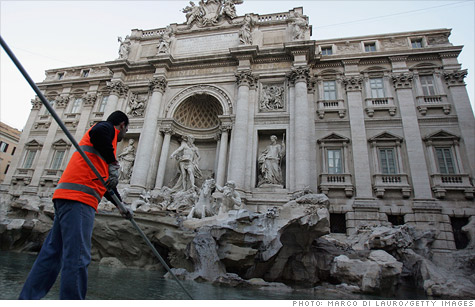 A worker fishes coins out of Rome's famous Trevi Fountain.