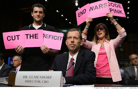 Before the debt committee hearing began Tuesday, protesters held up signs in view of committee members. CBO Director Douglas Elmendorf was the only witness to testify.