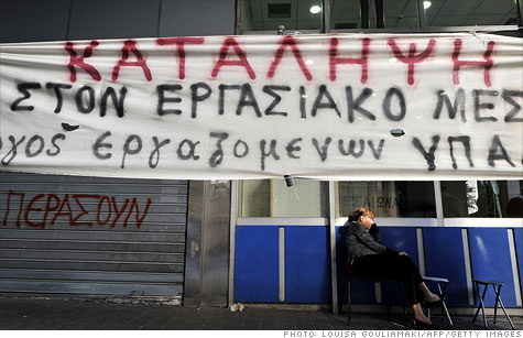 An employee sits by the occupied Ministry of Finance in Athens by a banner which translates as 'Occupation' on September 30, 2011