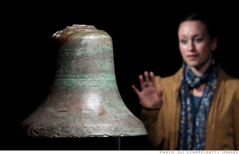 A woman examines the Titanic's crows nest bell in an exhibition of artifacts recovered from the wreck of the Titanic on November 3, 2010 in London