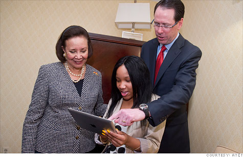 AT&T CEO Randall Stephenson shows off an iPad app to Washington high school student and 'Aspire' graduate Joylin Hayes and America's Promise Alliance Chair Alma Powell.