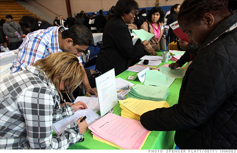 Job seekers fill out applications at a job fair in Queens, New York.