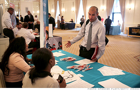 A job applicant speaks to perspective employers at a career fair in New York last week.