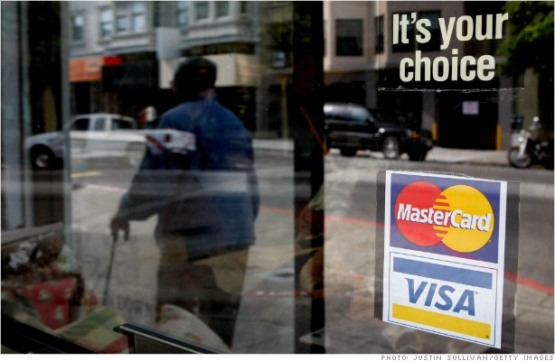 A window sticker advertising Visa and MasterCard credit cards hangs in
