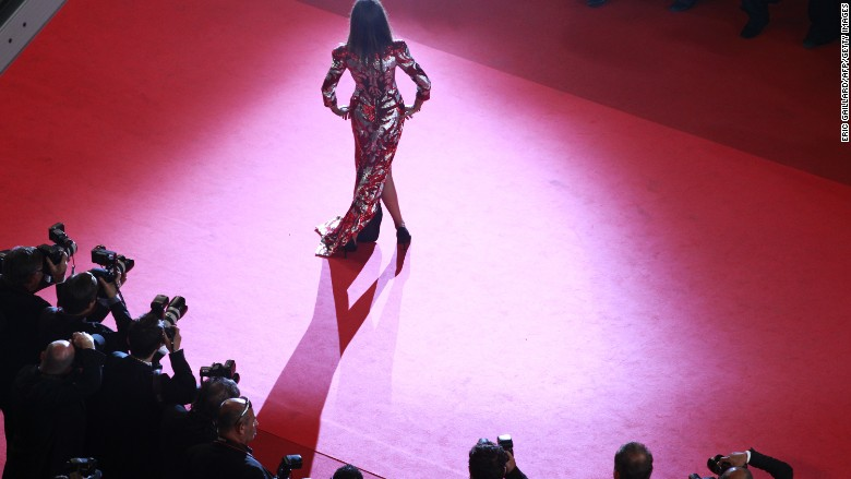 Caption:An unidentified guest poses on the red carpet before the screening of 'Drive' presented in competition at the 64th Cannes Film Festival on May 20, 2011 in Cannes. AFP PHOTO / POOL / Eric Gaillard (Photo credit should read ERIC GAILLARD/AFP/Getty Images)