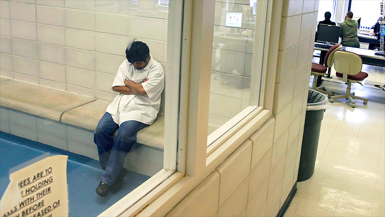 A person arrested by Immigration and Customs Enforcement officers sits in a detention room in ICE's New York headquarters.