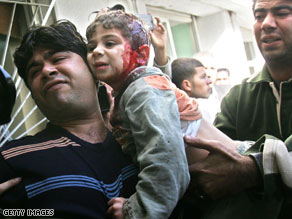 A man carries a wounded Palestinian boy into a hospital in Gaza City on Sunday.