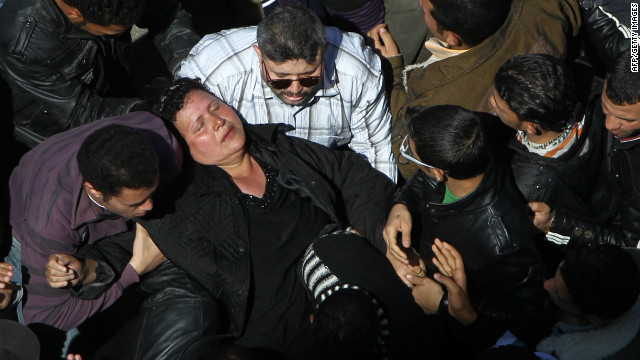 A woman faints as crowds converge on Saint Mark's Coptic Cathedral in Cairo's al-Abbassiya district, March 18, 2012