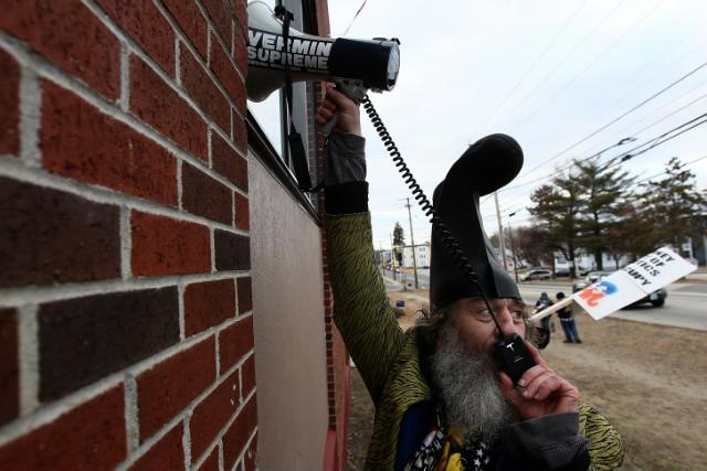 Vermin Supreme places a megaphone against a restaurant where Newt Gingrich is.
