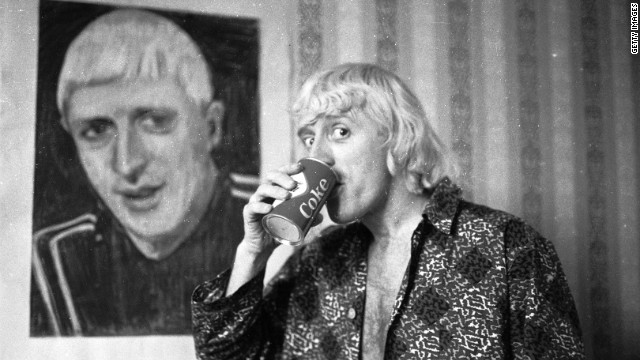 "Jimmy Savile, the first presenter of long-running music program ""Top of the Pops,"" poses by a portrait of himself in February 1965, while enjoying his regular breakfast of Coke and a cigar in a central London hotel room."