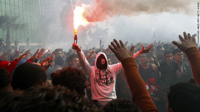 A fan of Al-Ahly football club lights a flare as club supporters celebrate outside its headquarters in Cairo on January 26.