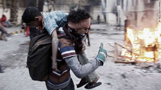An Egyptian protester carries an injured boy away from clashes with Egyptian riot police on January 26, in Cairo.