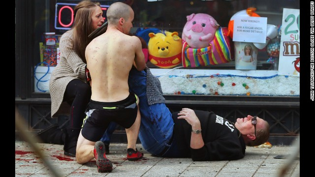 Passersby put pressure on a victim's leg to try to stop the bleeding at the scene of the first explosion.