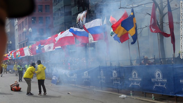 Officials watch as the first explosion goes off on Boylston Street in Boston.