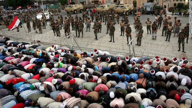 Supporters of Morsy pray next to the headquarters of the Republican Guards in Cairo on Saturday, July 6, during the funeral of seven people killed during clashes.