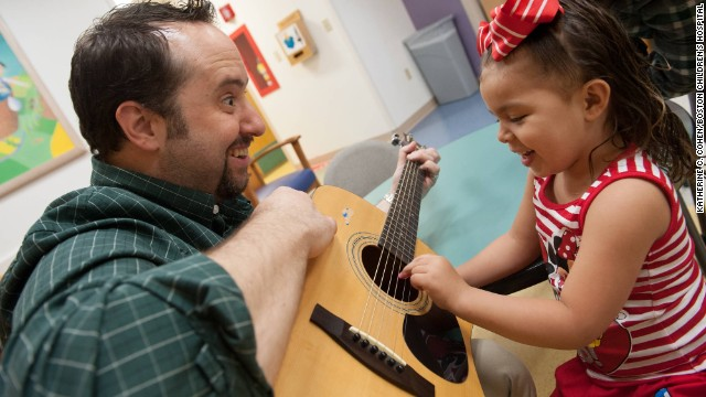 Brian Jantz, a music therapist at Boston Children's Hospital, plays with a patient, Yaneishka Trujillo.