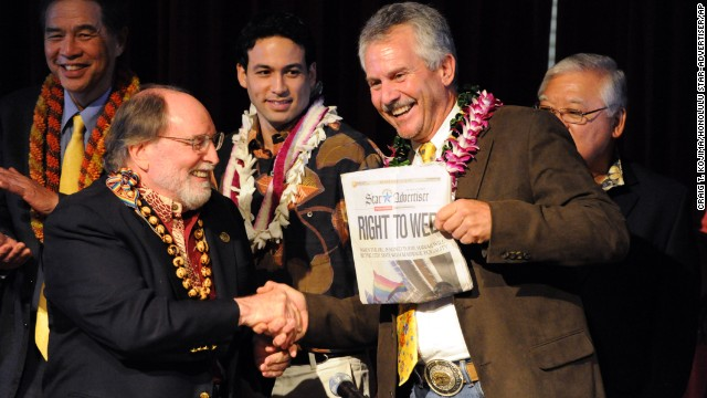Hawaiian Gov. Neil Abercrombie, left, and former Sen. Avery Chumbley celebrate with a copy of the Star-Advertiser after Abercrombie signed a bill legalizing same-sex marriage in Hawaii on Wednesday, November 13, in Honolulu. Hawaii's same-sex marriage debate began in 1990, when two women applied for a marriage license, leading to a court battle and a 1993 state Supreme Court decision that their rights to equal protection were violated by not letting them marry. Now the state is positioning itself for an increase in tourism as visitors arrive to take advantage of the law, which took effect December 2.