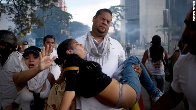 A man carries a woman overcome by tear gas from riot police at anti-government protesters in Caracas on Saturday, February 22.