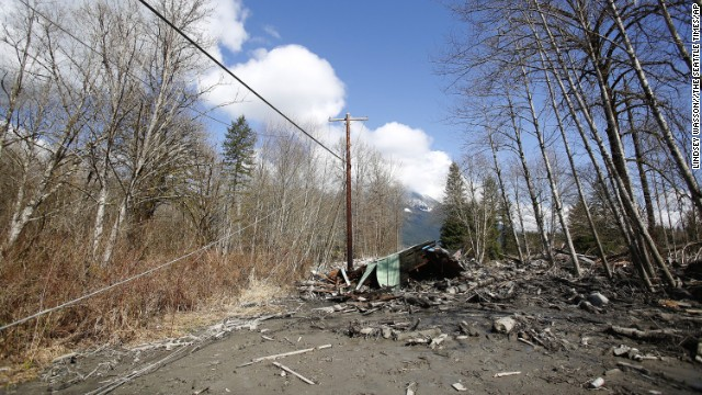 Downed power lines and parts of a destroyed house can be seen in the debris blocking the road near Oso.
