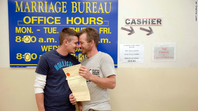 William Roletter, left, and Paul Rowe, right, press close to one another after having their photo taken with their newly acquired marriage certificate at City Hall in Philadelphia, Pennsylvania, on May 21.