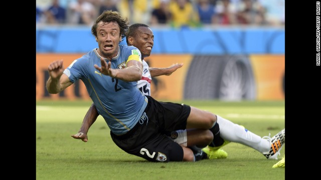Costa Rica defender Junior Diaz, right, tackles Uruguay's Diego Lugano.