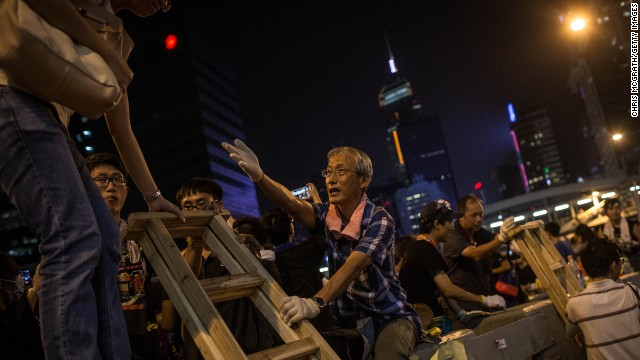 A man helps protesters use a makeshift ladder to climb over concrete street barricades on September 29.