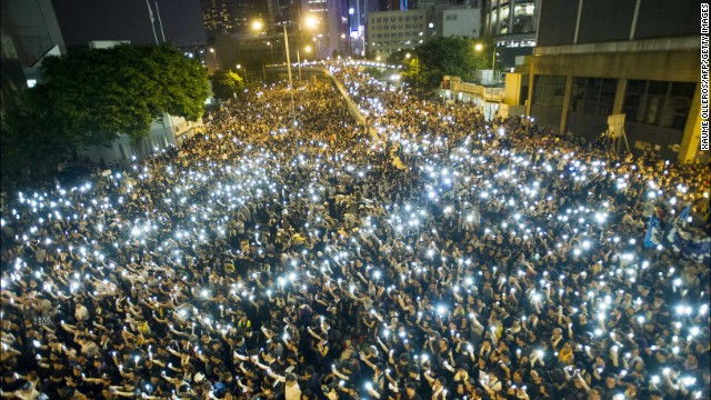 Protesters hold up their cell phones in a display of solidarity during a protest outside the Legislative Council headquarters in Hong Kong on Monday, September 29.