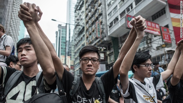 Pro-democracy protesters raise their arms in a sign of nonviolence as they protect a barricade from rival protest groups in the Mong Kok district on October 4.