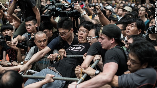 A pro-democracy protester holds on to a barrier as he and others defend a barricade from attacks by rival protest groups in the Mong Kok district on Saturday, October 4.