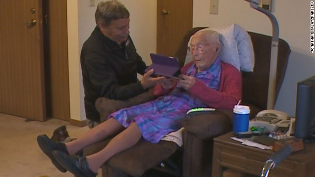 Anna Stoehr, a new Facebook user at age 114, checks out an iPad with the help of friend Joseph Ramireza.