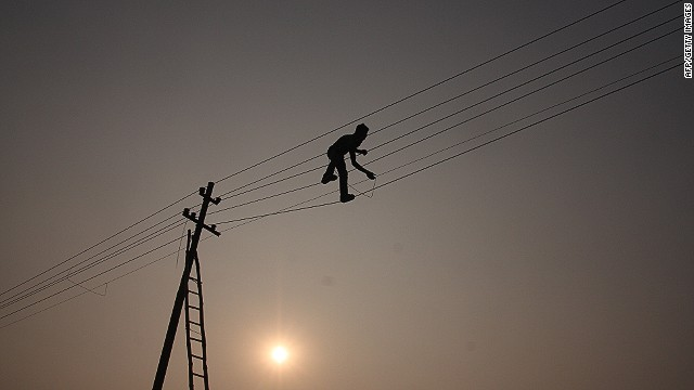 A workman attends to a power line in India. Energy theft remains a powerful disincentive for new investment in the sector.