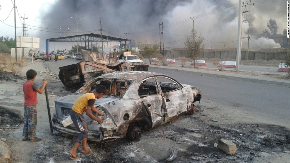 Children mount subsequent to a burnt automobile during clashes between Iraqi confidence army and ISIS militants in Mosul on Tuesday, Jun 10.